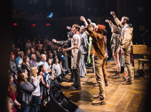 The Hadestown raises a glass to the audience at the end of the show. Catch them in action at Broadway's Walter Kerr Theatre.