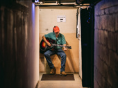 Props crew member Rob Dagna tunes a guitar.