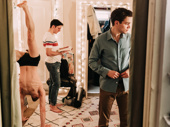 Samuel H. Levine and Andrew Burnap get dressed while Kyle Soller does a handstand.