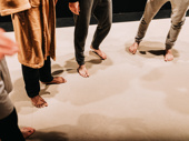 The cast warms up on stage before Part Two. They don't wear shoes when they're on stage for the show, so they walk around in slippers backstage.
