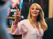 Model and actress Christie Brinkley flashes a peace sign at the press.
