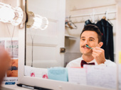 Mark Evans gets his mustache shipshape before the show.